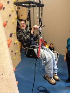 Tim Kunzier tries out the adaptive climbing harness at the Central Rock Gym.