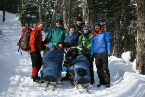 """Front L to R: Tim and Dew, in sleeping bags and on """"sit-skis,"""" on the way down the   Tuckerman Ravine Trail with the rest of the team (Rick, Jim, Joel, Dan, Julia, Adam)."""