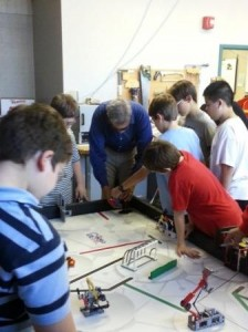 The team shows him some of the obstacle courses on the FLL table. Randy is using his hands to feel the obstacles as the kids describe what each does and how they program the robot to do the tasks.