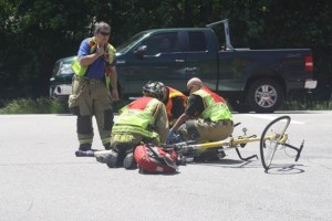 Emergency personnel attend to Brent Bell and his friend after they were struck by a car while riding a tandem bicycle.