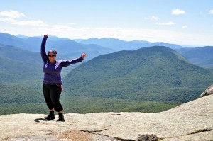 Tracy with arms up on the summit of a mountain.