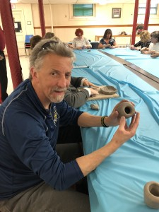 Randy holding a small unfinished clay piece at a table with blue covering, and looking at the camera.