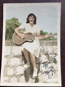 Picture of a young woman with a guitar sitting on a stone wall.