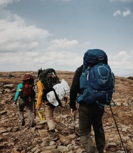 Hikers with full packs walk on a rocky trail.