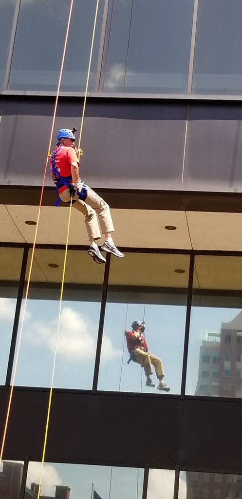 A photo of Randy descending from his rappelling adventure shows Randy in harness, hardhat, tan pants and red shirt and his reflection on the building just slightly below him.