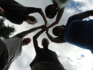 The team on the Southern Presi traverse hike share a high five. The camera captures their triumph from below.