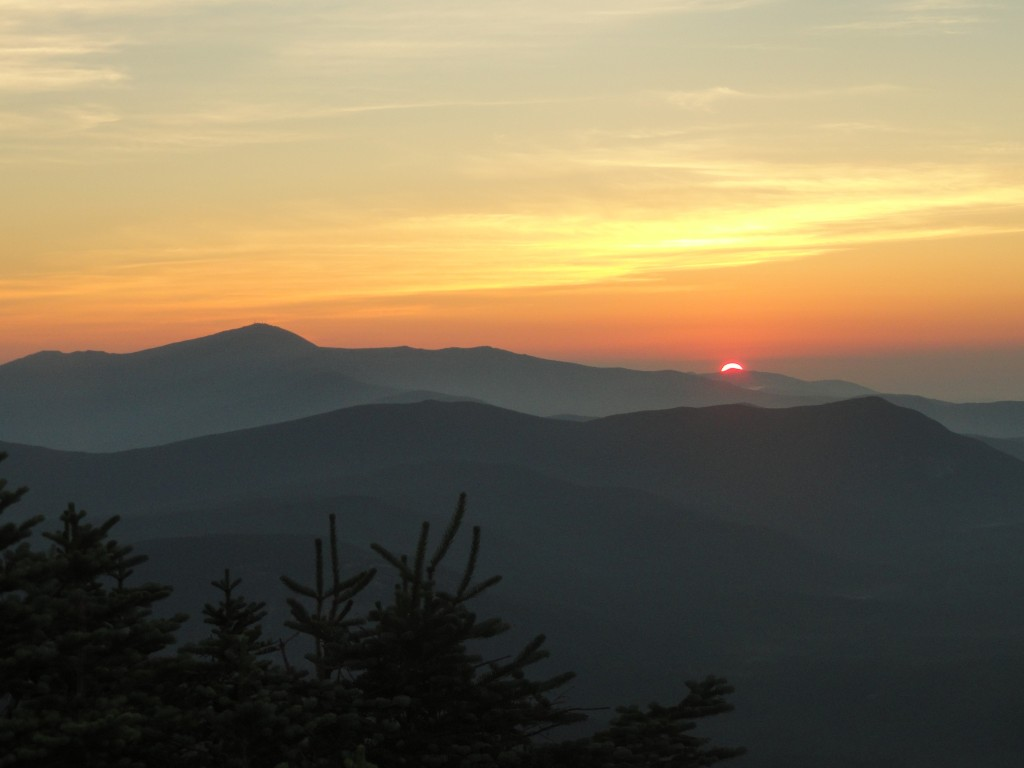 A brilliant orange sun begins to rise above the darkened southern presidential range - as seen from Mt Bond. The sky is a firey orange to yellow fading into a light blue.