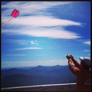 Robert flies a small pink kite on the summit.