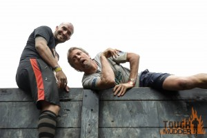 Randy mugs for the camera with Greg on top of an obstacle