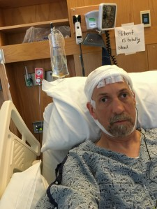 Randy sits in a hospital bed with a bandage wrapped around his head and an IV.