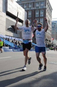 Jose and Randy with their hands up running the Marathon.
