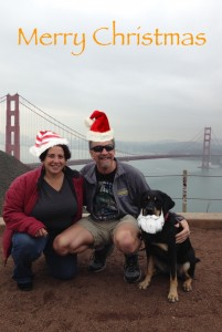 Randy, Tracy and Autumn sport christmas hats and a beard in front of the Golden Gate Bridge