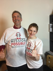 Christopher and Randy posing proudly in their Mission Possible T-shirts after recording an episode of Christopher's popular podcast show