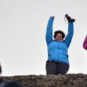 Tracy with her arms up on a summit.