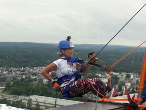 Woman in workout gear, helmet and repelling harness is poised on the edge of a building