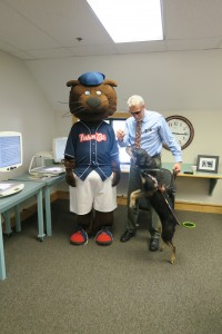 Autumn meets Fungo, the mascot of the Fishercats. Dog jumping up while Randy looks down at her.