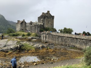 Eilean Donan Castle up on the hill with a cloudy sky