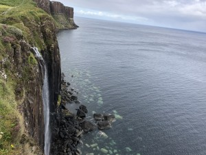 View of Mealt Falls and Kilt Rock, Isle of Skye. Dramatic waterfall flowing into the ocean, with a cloudy sky.