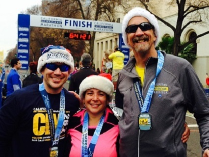 At the finish line of the 12/7/14 California International Marathon in Sacramento CA...Left to right Jose Acevedo, Tracy Pierce and Randy Pierce--all wearing their newly earned race medals around their necks. All are beaming and wearing New England Patriots Santa hats.