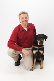 Picture of Randy kneeling with his  				Guide Dog, Autumn, close by his side.