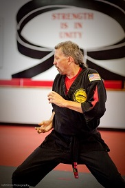 Picture of Randy at a dojo, working on his karate, wearing a Karate uniform