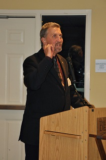 Picture of Randy standing at a podium,  				gesturing to his ear, while speaking to an audience.