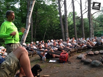 Picture of Randy presenting to a large circle of campers in an outdoor setting