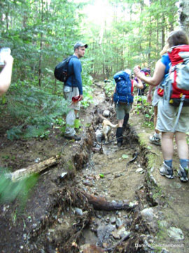 The group hikes a very muddy trail.