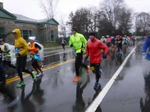 Randy and Jose run the Boston Marathon in 2018, bundled up in coasts on a rainy street.
