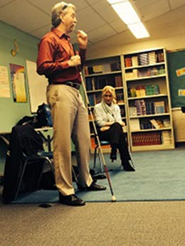 Randy stands with his cane, speaking to a classroom of students.