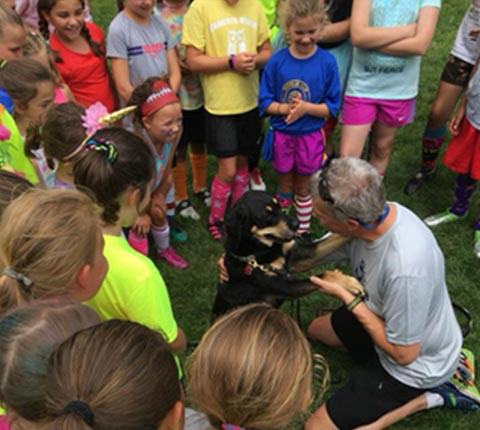 Autumn is giving Randy an adorable hug while a group of young soccer camp attendees look on with appreciation!""