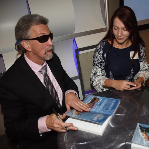 Randy sits at a table with two copies of See You at the Summit in front of him. He is wearing a dark suit and pink tie. Robbie looks on as he prepares to sign.