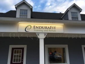 Photo shows a storefront with the Endurafit logo sign on the roof above a door and window.