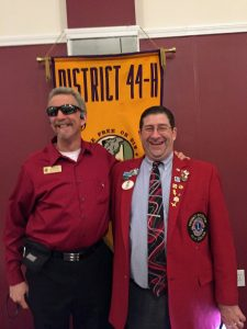 Randy and Past District Governor Scott Wilson stand in front of a Lions flag both smiling broadly