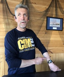 Randy stands in a well lit room wearing a dark blue shirt with the letters CIM on it and pointing to his outstretched arm with an apple watch on it.