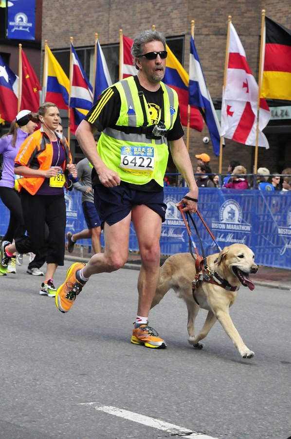 Randy and Quinn crossing the finish line of the 2013 BAA 5K. Quinn, a yellow Labrador Retriever is guiding with one paw on the ground, tongue joyfully hanging out as they pass the flag display which marks the Boston Marathon finish.
