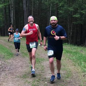Tom and Randy running on a local trail, both coming toward (and looking at) the camera. Both are showing big smiles!
