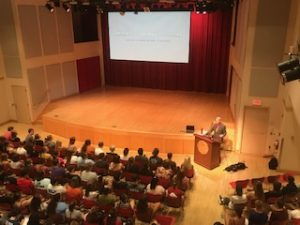 Randy giving a presentation at Keene State in an auditorium full of college students.