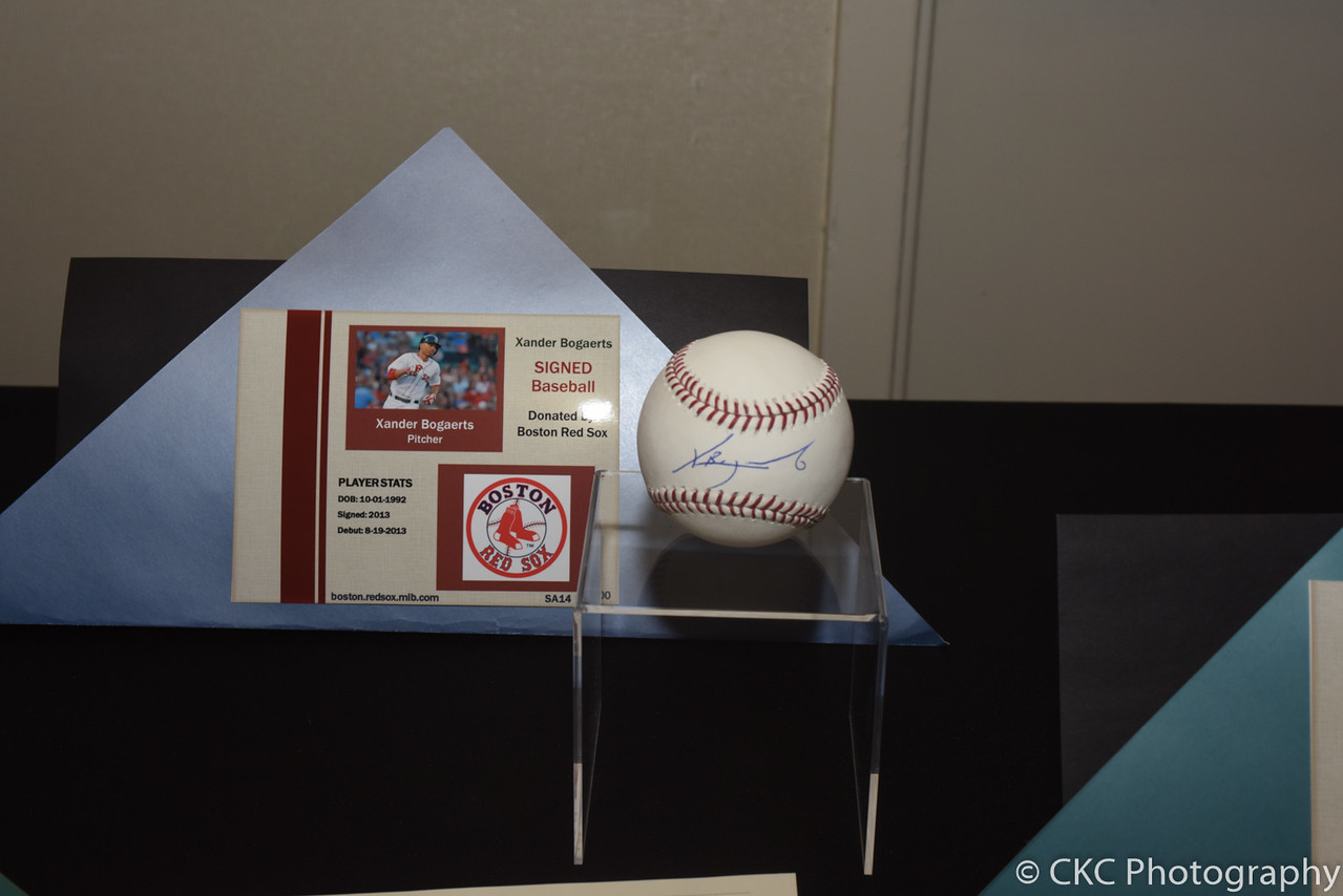 A baseball signed by Red Sox player Xander Bogaerts on a small stand in front of a sign describing it