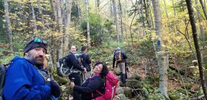 Several people climb up the stony mountain trail surrounded by woods, some looking back at smiling.