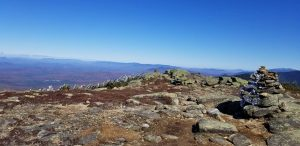 A colorful rock summit with a bright blue sky and a distant ridge line.