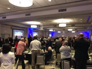 A banquet room full of people giving a standing ovation.