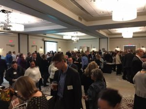 A large crowd of people mills around a room with appetizers and silent auction items.