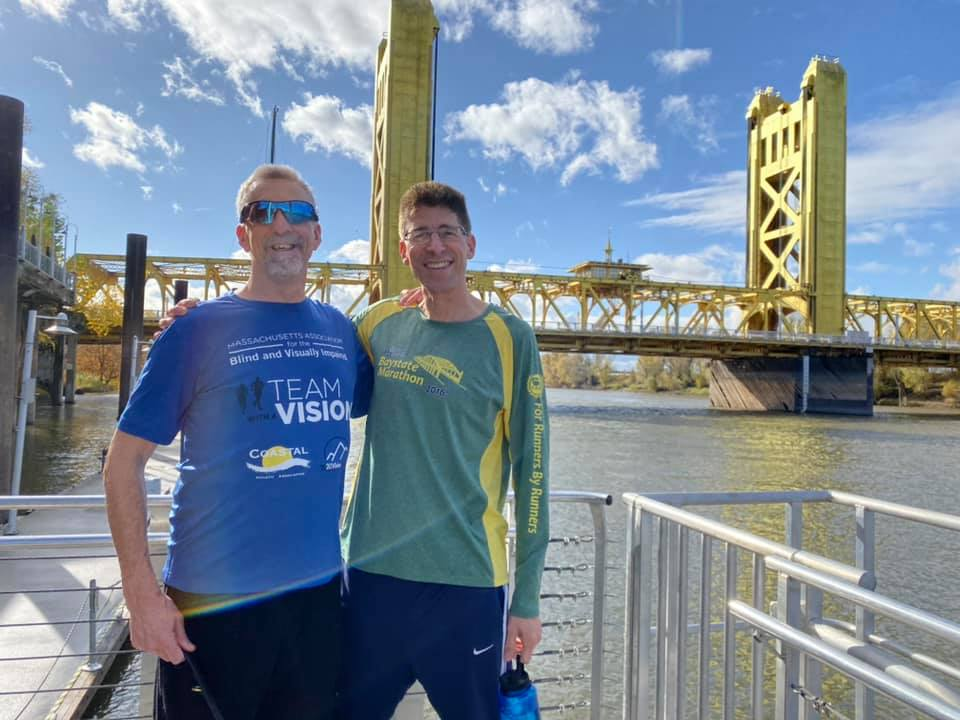 Randy and Rob (two tall guys in running gear) pose smiling in front of a blue sky and yellow steel bridge backdrop.