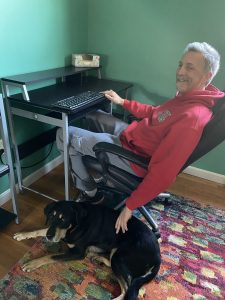 Randy sits at his desk in a greek room in front of a keyboard with Autumn on the floor by his side. He is petting her.