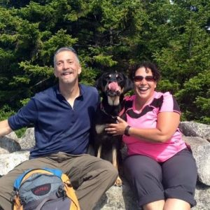 Randy, Tracy and Autumn laughing on a summit peak. Tracy wears a bright pink top and Autumn is caught with her pink tongue out in the middle of licking her own nose.