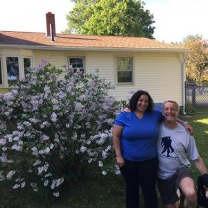 Randy and Tracy in front of a large lilac bush with a house behind them.
