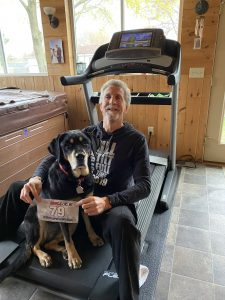 "Randy and Autumn sit on a treadmill in a sunlit room, with Randy holding a runner bib that says ""79"""