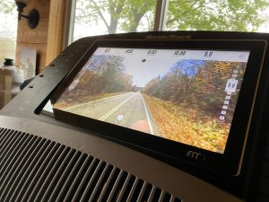 Treadmill with image on the viewscreen of an autumn road along a highway